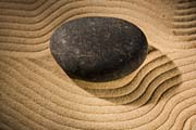 Hot Stone Massage. pebble on wavy sand